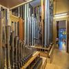 Two groups of organ pipes inside the Bigelow organ chamber at Saint Ambrose Church, with stained glass window seen through door.