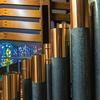 Closeup of copper-topped organ pipes and exterior organ casing, seen from inside the Bigelow organ at Saint Ambrose Church, with stained glass window in the background.